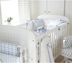 White cot with blue accessories