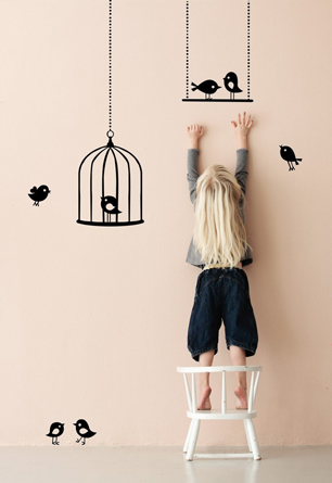 little girl putting up birdcage wall stickers