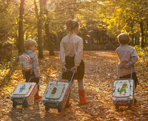 three children in woods with Pink Lining bags