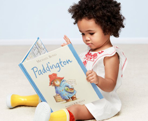 little girl reading Paddington Bear book