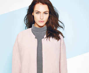 model wears pink coat and grey jumper